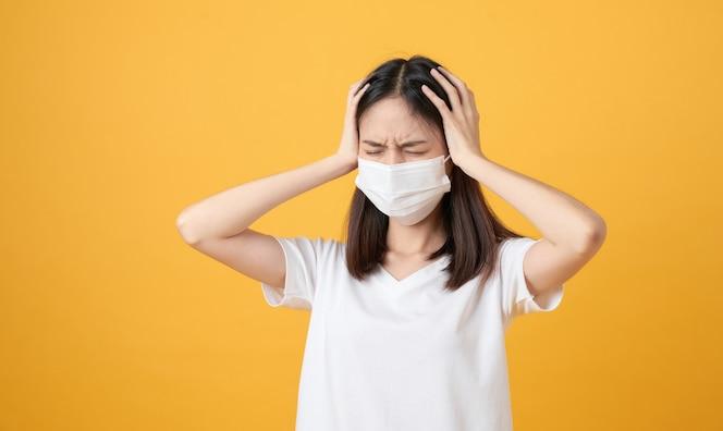 Las mujeres asiáticas usan máscaras para proteger las enfermedades y el dolor de cabeza de un virus