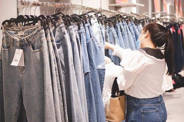 Las mujeres asiáticas usan mascarilla quirúrgica elegir jeans en grandes almacenes