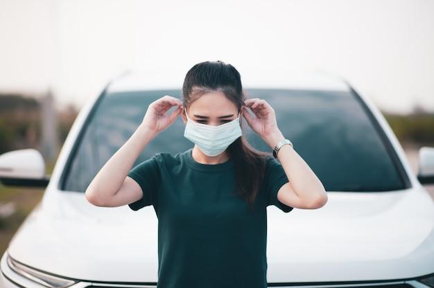 Las mujeres asiáticas usan mascarilla quirúrgica o mascarilla en el automóvil estacionado al aire libre