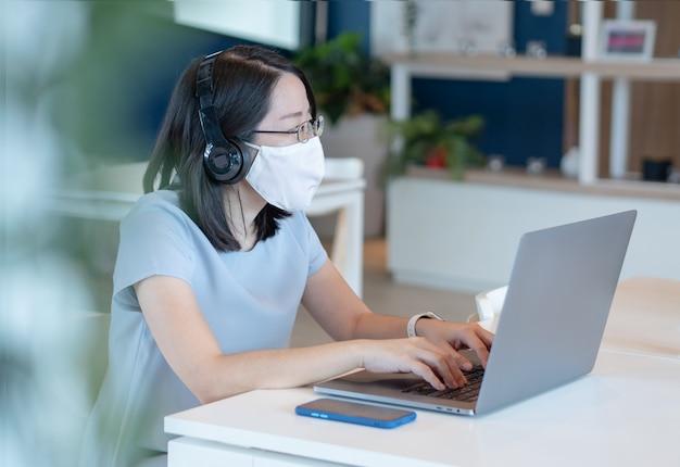 Las mujeres asiáticas usan mascarillas, usan teléfonos inteligentes y computadoras portátiles, se sientan en mesas separadas para mantener el distanciamiento social de seguridad.