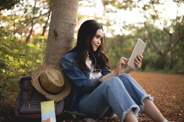Las mujeres asiáticas ven la tableta con el sombrero al atardecer.