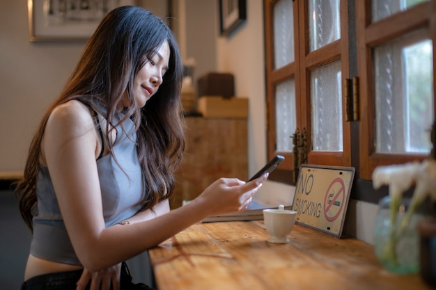 Las mujeres asiáticas verifican la información del teléfono celular en la cafetería