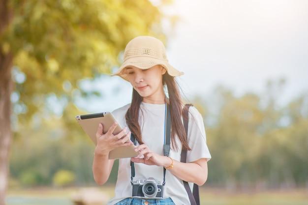 Las mujeres asiáticas viajan en la naturaleza con tableta tomando fotos