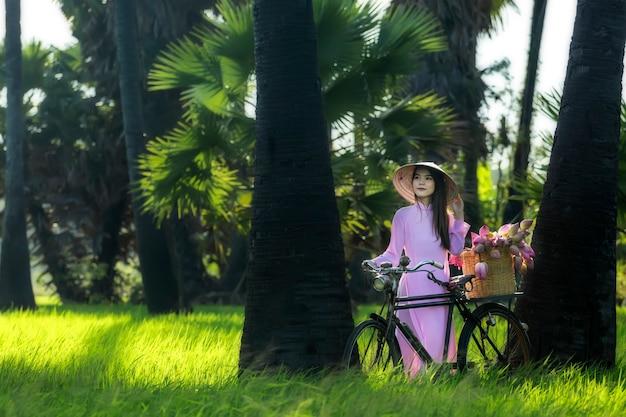 Las mujeres asiáticas vietnam es una niña en bicicleta para ir a la tienda después de la cesta de flores de loto.