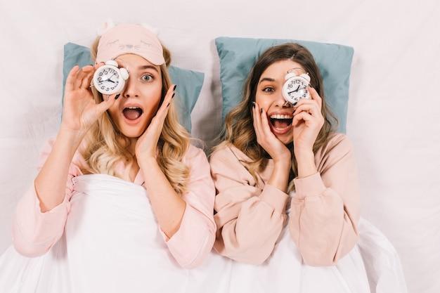 Mujeres asombradas acostado sobre almohadas azules en la cama