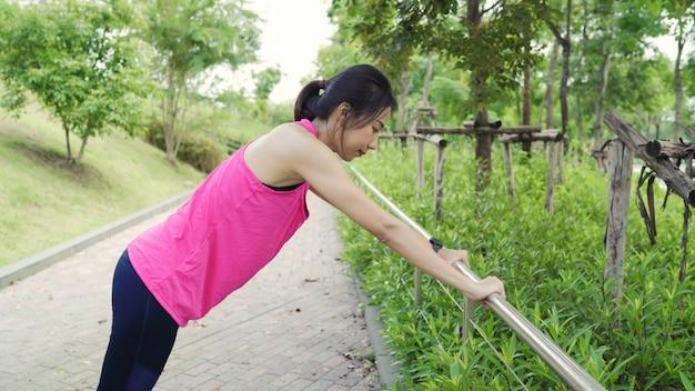 Mujeres atléticas asiáticas jóvenes hermosas hermosas en las piernas de la ropa de los deportes que se calientan y que estiran sus brazos