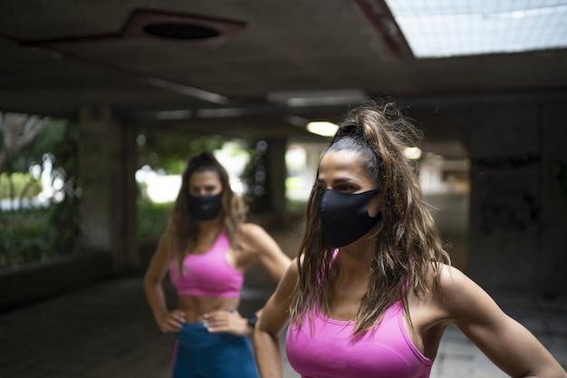 Mujeres atléticas caucásicas corriendo y haciendo entrenamientos matutinos con máscaras médicas