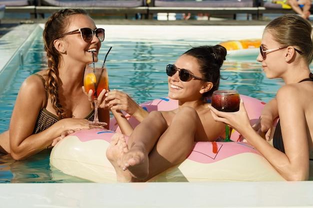 Mujeres atractivas disfrutando el caluroso día de verano en la piscina
