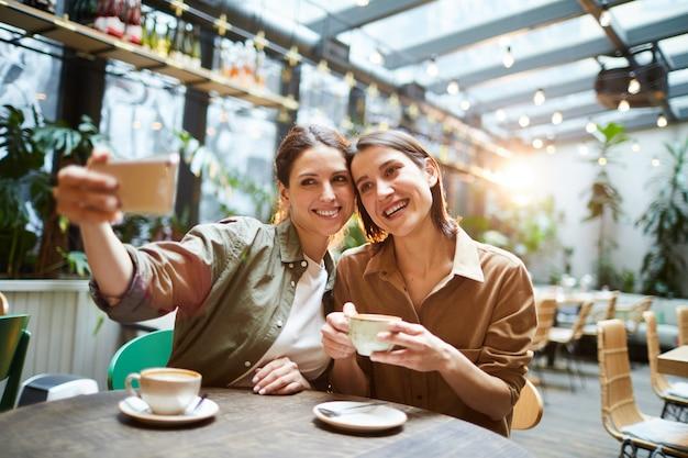 Mujeres atractivas fotografiando juntos en la cafetería.