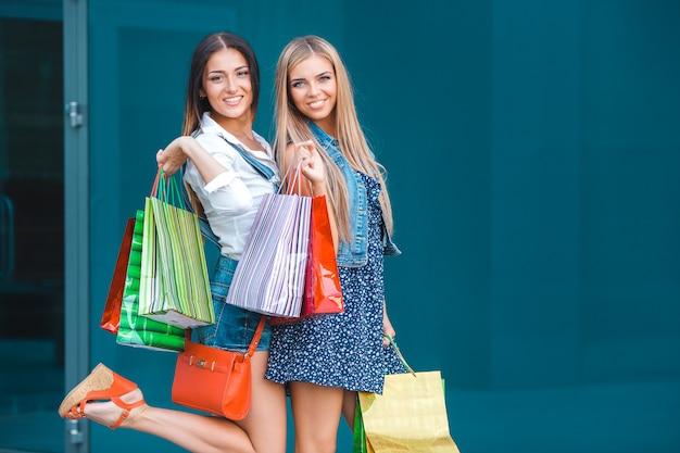Mujeres atractivas jóvenes con bolsas de compras al aire libre