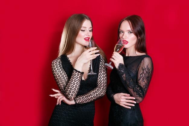 Mujeres atractivas jóvenes celebrando una fiesta, bebiendo champán