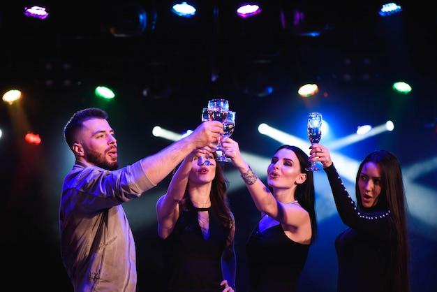 Mujeres atractivas jóvenes y hombre celebrando una fiesta, bebiendo champán y bailando.