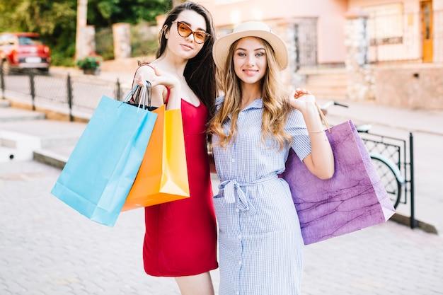Mujeres atractivas posando con bolsas de papel