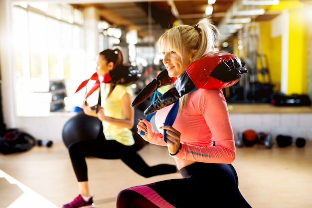 Mujeres atractivas que trabajan sentadillas en el gimnasio.
