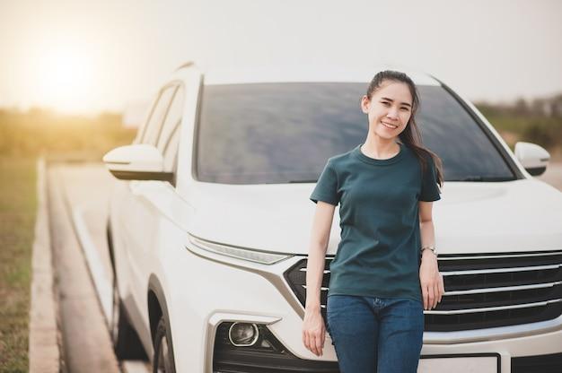 Las mujeres en el automóvil estacionado en la carretera y el asiento pequeño para el automóvil en la carretera utilizado para viajes diarios