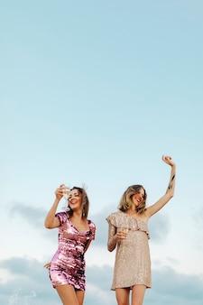Mujeres bailando con copas de champán en la playa.
