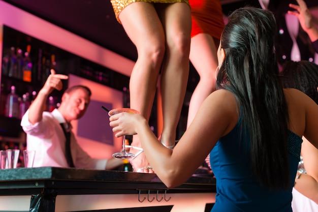 Las mujeres en el bar o en el club están bailando sobre la mesa