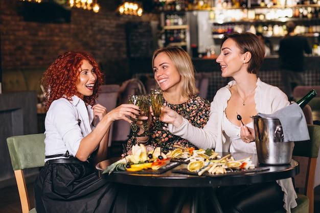 Mujeres en el bar que tienen charla dinking cocktails