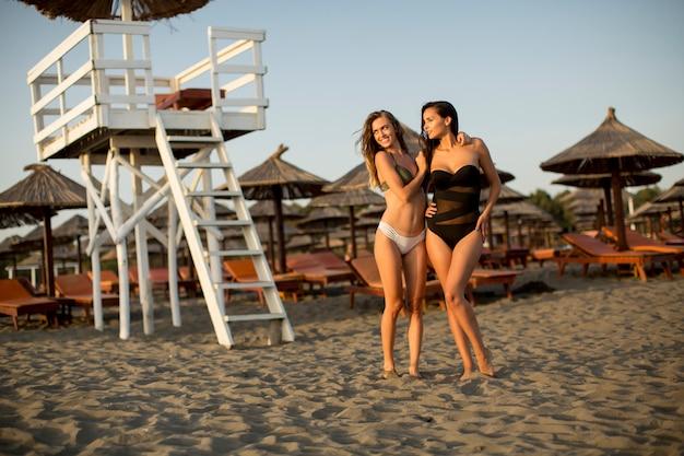 Mujeres bastante jovenes que se relajan en la playa arenosa