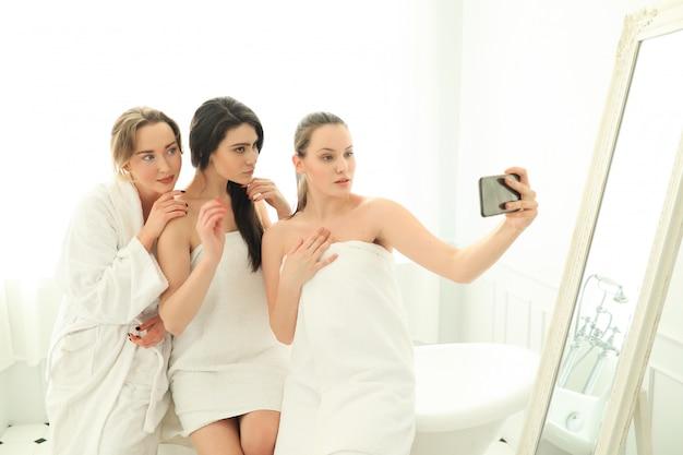 Mujeres con bata de baño y toallas.