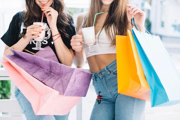 Mujeres con batidos y bolsas de papel