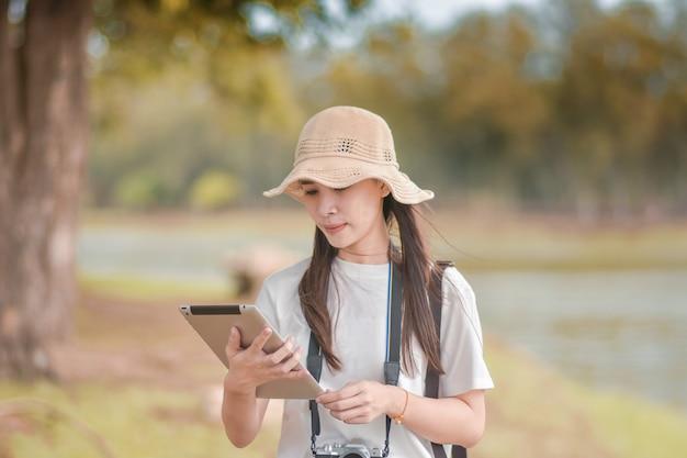 Las mujeres de la belleza que sostienen la tableta con viaje de la cámara toman la foto
