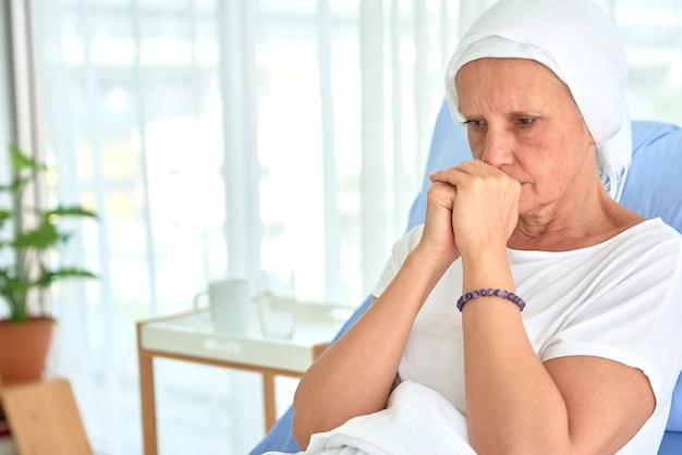 Las mujeres blancas caucásicas sin pelo y sin cejas se sienten mal están orando y esperando la quimioterapia en la habitación del hospital, concepto del mes de concientización sobre el cáncer de mama.