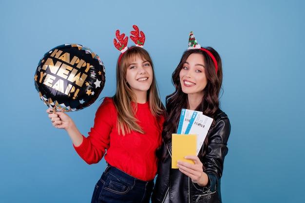 Mujeres con boletos de avión y feliz año nuevo globo aislado sobre azul