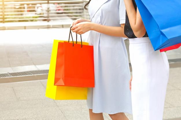 Mujeres con bolsas de compras caminando por el cielo.