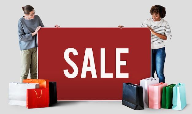 Mujeres con bolsas de compras y una pancarta