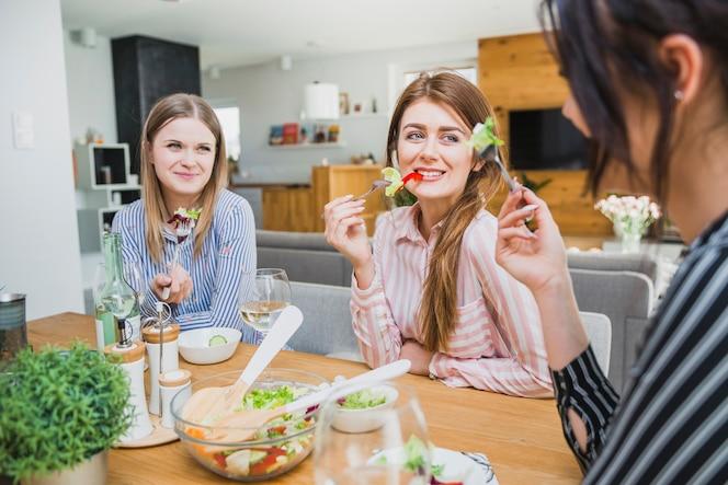Mujeres bonitas comiendo en la mesa y sonriendo