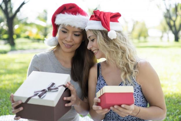 Mujeres bonitas felices con sombreros de santa y mirando furtivamente en una caja de regalo