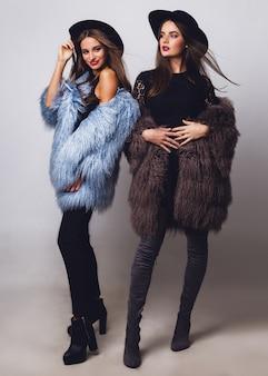 Mujeres bonitas glamorosas posando y vistiendo abrigos de piel