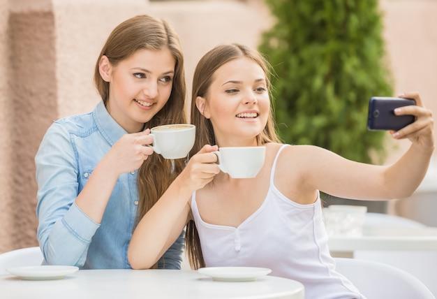 Mujeres bonitas jóvenes tomando selfie con café.