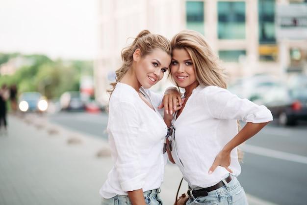 Mujeres bonitas y de moda abrazándose, caminando juntas