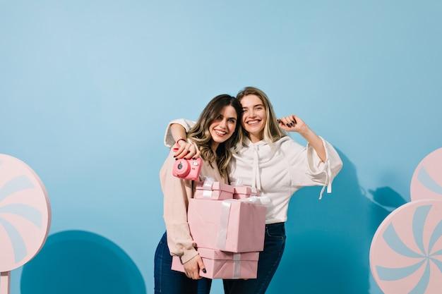 Mujeres bonitas con regalos abrazando en pared azul