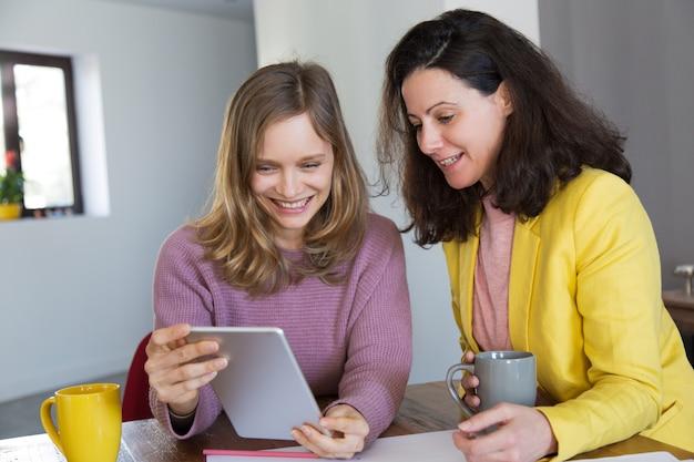 Mujeres bonitas sonrientes bebiendo té y usando tableta