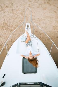 Mujeres bonitas tumbado en la cubierta del yate y disfrutando de relajarse en la playa