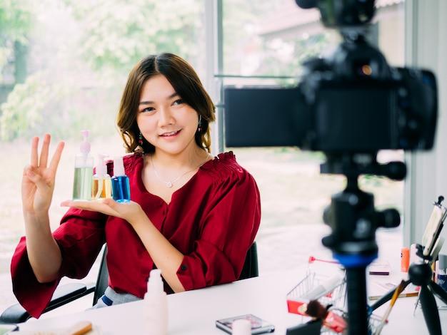Las mujeres bonitas de vloger usan internet en línea para revisar su marca de cosméticos