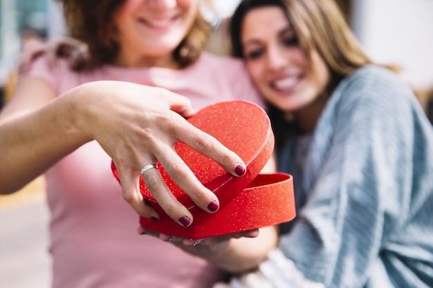 Mujeres borrosas abriendo la caja en forma de corazón