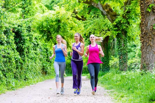 Mujeres en el bosque corriendo por deporte.