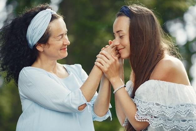 Mujeres en un bosque de verano. dama con un vestido azul. familia posando y abrazándose.