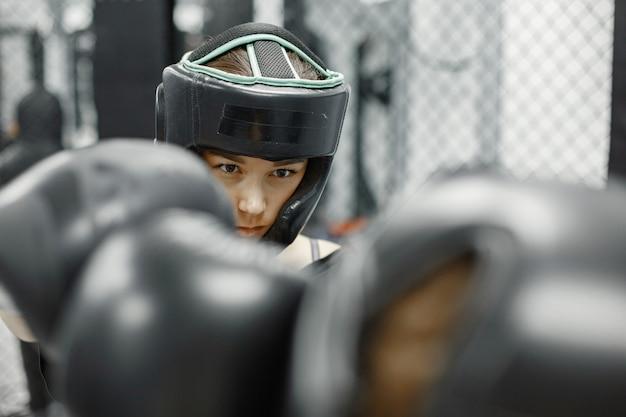Mujeres de boxeo. principiantes en un gimnasio. dama en ropa deportiva negra.