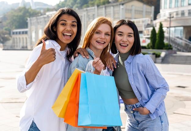 Mujeres calzando sus bolsas de compras al aire libre