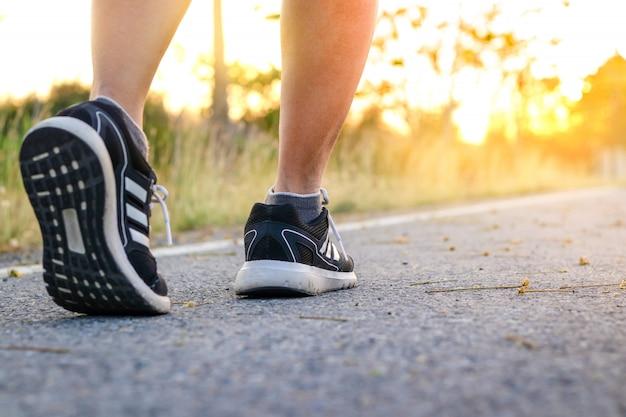 Las mujeres caminan haciendo ejercicio en la noche, viendo la luz naranja del sol aire fresco