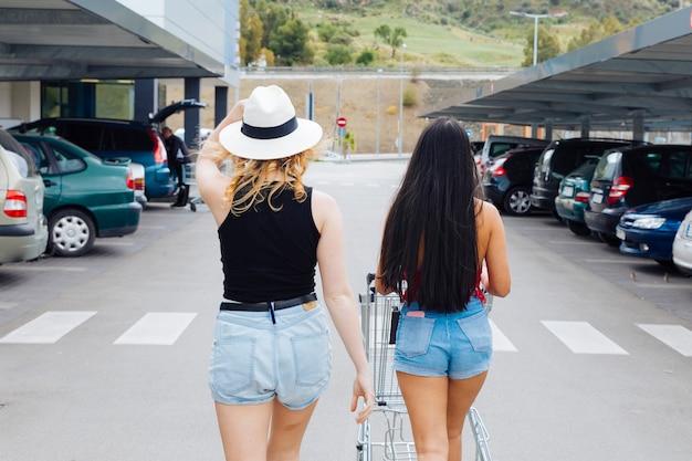 Mujeres caminando al carro con productos en carro de compras del supermercado.