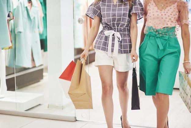 Mujeres caminando con bolsas de compras en el centro comercial