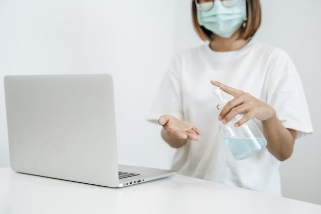 Mujeres con camisas blancas que presionan el gel para lavarse las manos y limpiarse las manos.