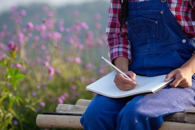 Mujeres campesinas están tomando notas en el jardín de flores.