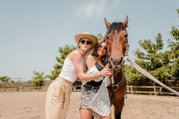 Mujeres en un campo caminando con un caballo.